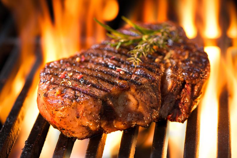 Steak auf einem Grillrost über Feuer