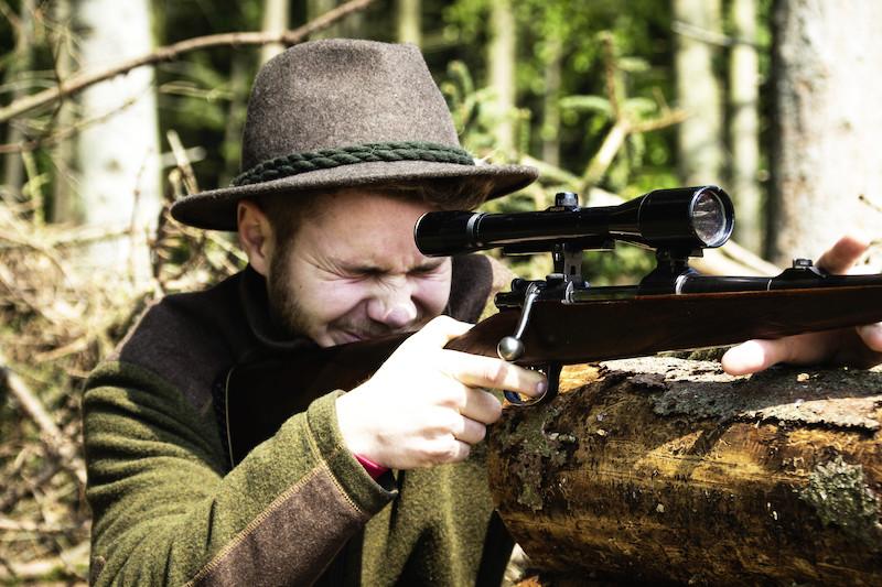 Jäger hinter seiner Waffe beim Mucken