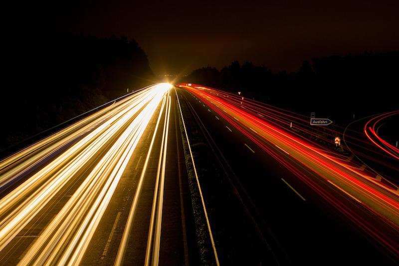 Vorbeifahrende Autos auf Autobahn bei Nacht