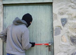 Einbrecher mit Brechstange an einer Tür
