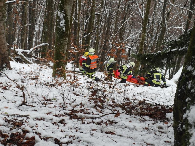 Feuerwehrleute retten Jäger bei Schnee aus steilem Hang im Wald