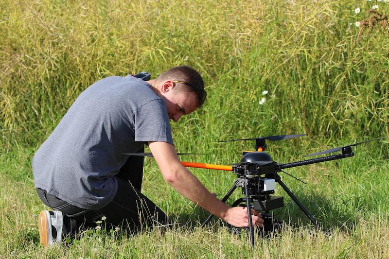 Pilot neben einer Drohne auf einer Wiese