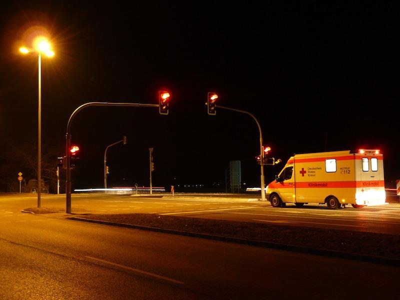Krankenwagen an einer roten Ampel in der Nacht