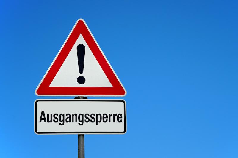 """Straßenschild mit der Aufschrift """"Ausgangssperre"""""""
