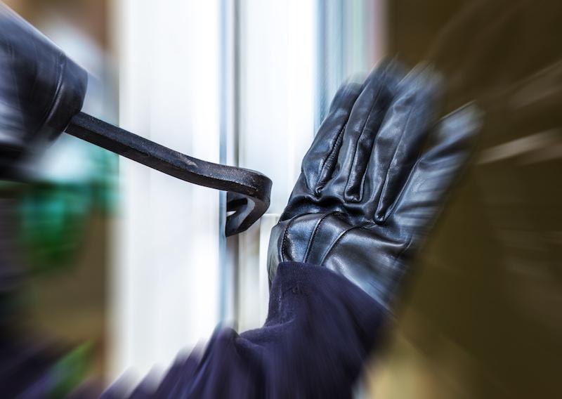 Einbrecher hantiert mit einem Brecheisen an einem Fenster