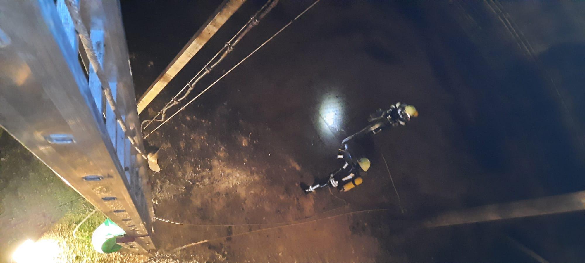 Feuerwehrleute mit Atemschutzausrüstung in einem Silo